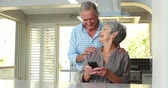 golden : Senior couple using smart phone at home Stock Footage