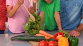 freshness : Family preparing salad together in kitchen