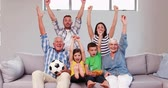 livingroom : Multi generation family celebrating goal sitting on sofa Stock Footage