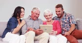 livingroom : Multi generation family using tablet on sofa Stock Footage