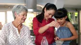 хром : Little girls, grandma and his mom preparing a cake in the kitchen Стоковые видеозаписи