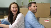 brother : A family of four unpacking boxes in a new house Stock Footage
