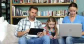 working parents : Two parents with her daughter using technologies in the lounge