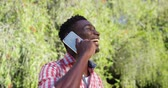 close up : Portrait of man is talking on the phone in a park Stock Footage