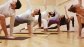 ginásio : Trainer assisting group of people with stretching exercise in fitness studio