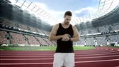 comovente : Male athlete setting a smartwatch while warming up in the a stadium