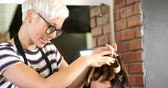 style : Female hairdresser styling customer hair in hair salon 4k Stock Footage