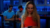 communication : Stylish woman text messaging and two men sitting at table at the bar 4K