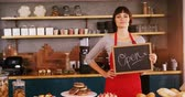 Smiling waitress showing a open sign board in cafe 4k Stok Video