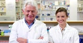 dispanser : Portrait of smiling pharmacists standing with arms crossed in pharmacy Stok Video