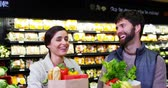 frondoso : Couple shopping for fruits and vegetables in organic section in supermarket