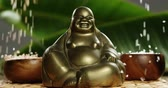zen like : Close-up of laughing buddha figurine with falling pearl on a mat 4k