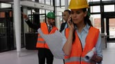 communication : Female architect talking on mobile phone in office while colleagues discussing over blueprints 4k Stock Footage