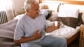 irritable : Sick senior man suffering from stomach ache holding his stomach in bedroom 4k