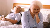 irritable : Worried senior woman sitting on bed in bedroom 4k