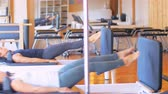 denge : Women exercising on gym equipment in fitness studio