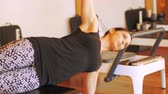 denge : Woman performing stretching exercise in fitness studio