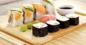 soja : Close-up of various sushi on tray with sauce on wooden table