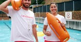 bóia : Portrait of swim coaches standing with inflatable floater near poolside