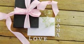fragility : Close-up of gift box with mama love text on wooden plank Stock Footage
