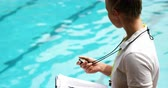 internovat : Swimming coach holding clipboard and looking at stopwatch at the leisure center
