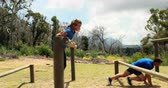 difícil : Fit man and woman climb a hurdles during obstacle course in boot camp Vídeos