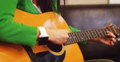 pessoas : Woman playing guitar in living room at home Stock Footage