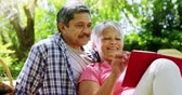paper : Senior couple reading book at the park Stock Footage