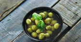 уксус : Close-up of green olives in vinegar garnished with herb