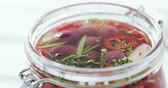 preserved : Close-up of pickled olives and herbs in a jar Stock Footage