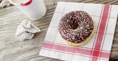 indulgence concept : Lipstick mark on coffee cup and chocolate doughnut with sprinkles on wooden table