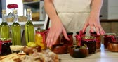 przetwory : Female staff arranging olives, preserves and olive oil on counter in organic market