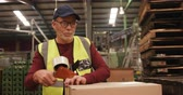 tape dispenser : Worker packing box in warehouse in bottle factory