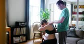 barriga : Man massaging pregnant woman shoulder at home Stock Footage