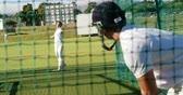batedor : Cricket players practicing in the nets during a practice session on cricket ground
