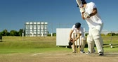 batedor : Wicket keeper collecting ball behind stumps on cricket field