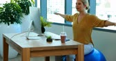 wellbeing : Female executive doing exercise on exercise ball at her desk in office Stock Footage