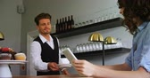 coat : Waiter serving coffee to costumer at counter in restaurant