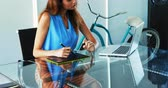 digitalizador : Female executive working over laptop and graphic tablet at desk in office 4k