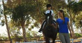 adult : Mother assisting daughter during horse riding in ranch 4k Stock Footage
