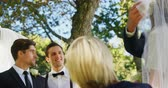 groomsmen : Groom happily looking at bride and her father while lifting her veil 4K 4k Stock Footage