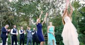 groomsmen : Bride throwing wedding bouquet to wedding guest at wedding 4K