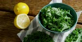 citrus fruit recipe : Close-up of green leafy vegetable in a bowl on wooden table 4k Stock Footage