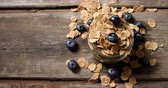mason jar : Jar filled with wheat flakes and blueberries on a wooden table 4k