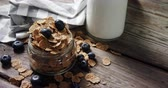 mason jar : Jar filled with wheat flakes and blueberries on wooden table 4k