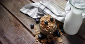 каменщик : Jar filled with wheat flakes and blueberries on wooden table 4k