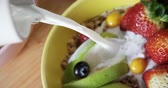 doğrama : Close-up of milk being poured on a healthy breakfast 4k