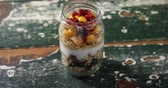 łyżka : Yogurt with pomegranates and golden berries in glass jar on a wooden table 4k