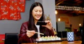 indulgence : Woman taking photo of sushi with mobile phone in restaurant 4k Stock Footage