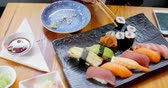 indulgence : Woman placing sushi in a plate at restaurant 4k Stock Footage